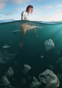 As part of an anti plastic campaign to keep plastic (plastic bags) out of our Oceans and to help keep our water and enviroment clean, a photo of a female surfer sitting on her surfboard as she floats out in the ocean with a view under the water of plastic bags floating in the water, which have the appearence of Jelly Fish in this coneptual photograph by Weston Fuller for a personal project about anit plastic in our enviroment.